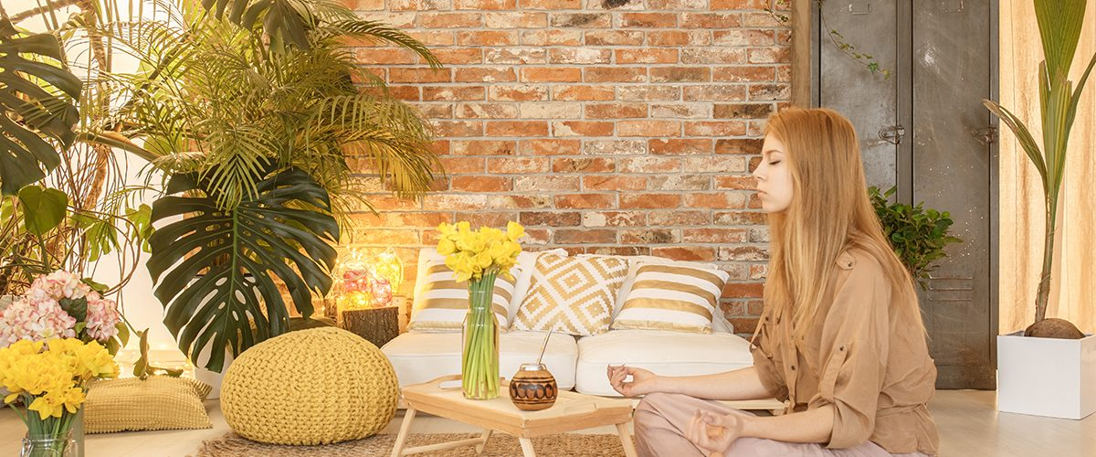 Young girl meditating in cozy natural room with red brick wall