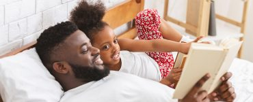 Bedtime story. Caring african dad reading book to his daughter at bedroom, free space