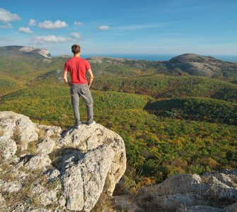 Man standing on the edge of cliff mountain. Conceptual scene.