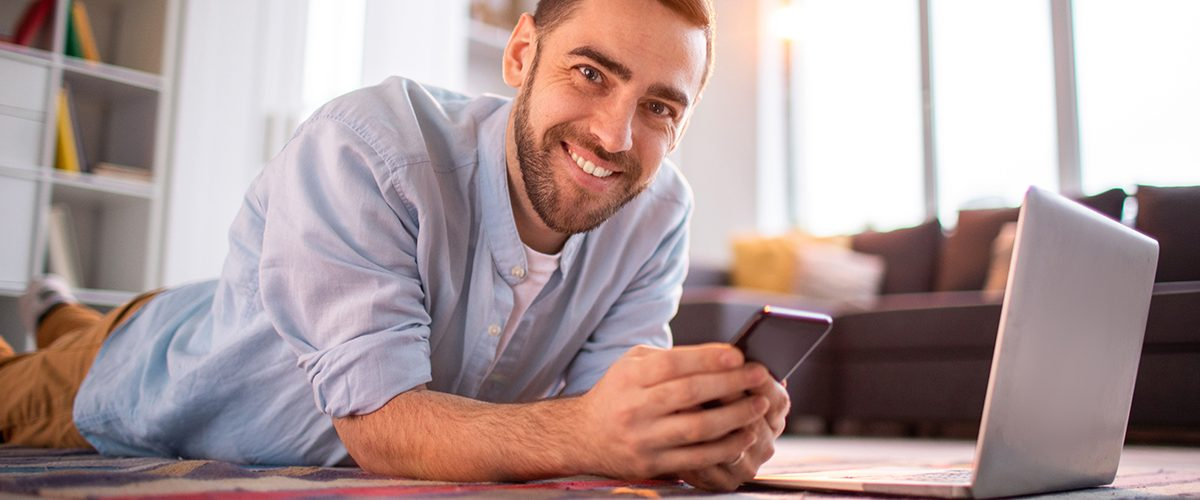 Cheerful young man in casualwear lying on the floor of living-room in front of laptop and scrolling in smartphone