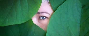Female eye behind big green leaves