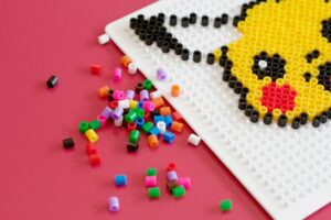 Perler bead Pikachu face on the perler bead board and assorted colors of beads scattered off to the side.