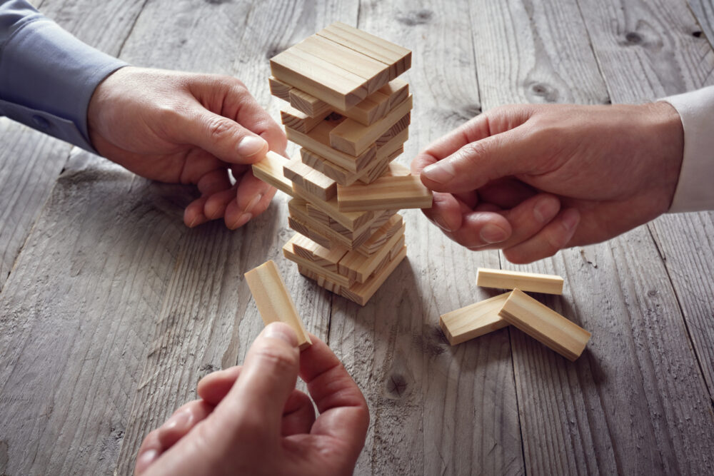 Hands playing a wooden block game on a table