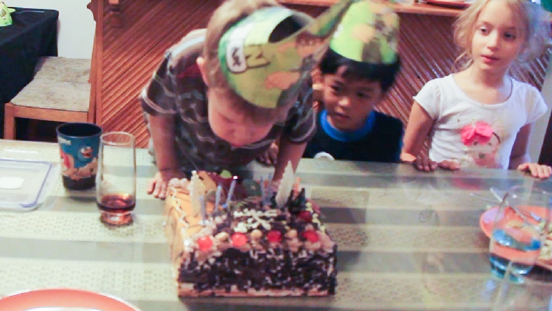 Blowing out candles from on his second cake.