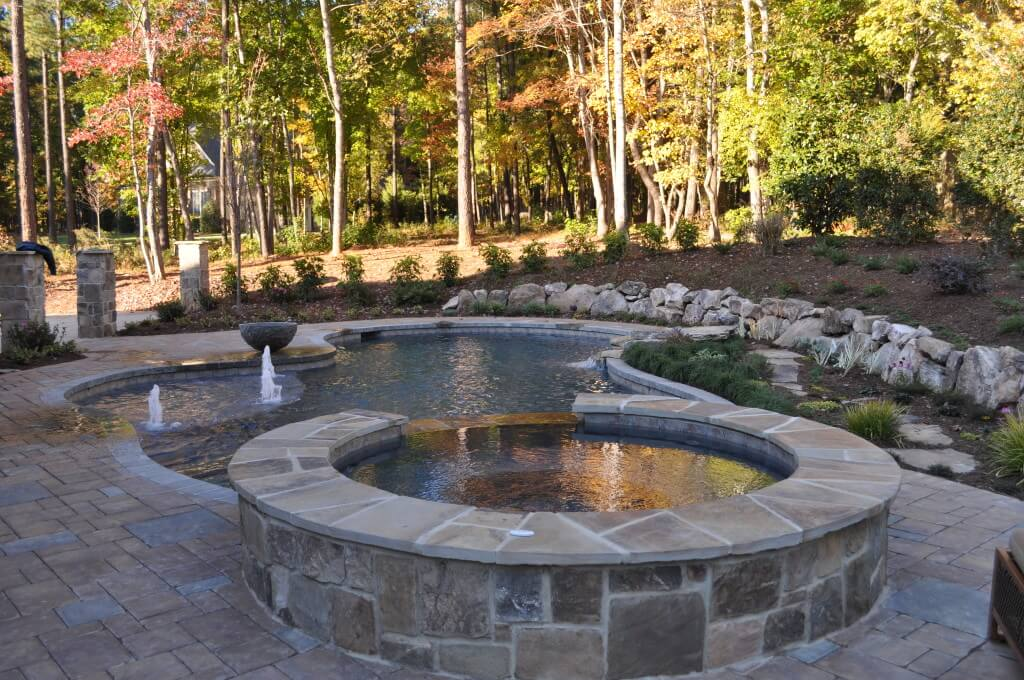 Custom freeform pool with spa and natural stone surround.