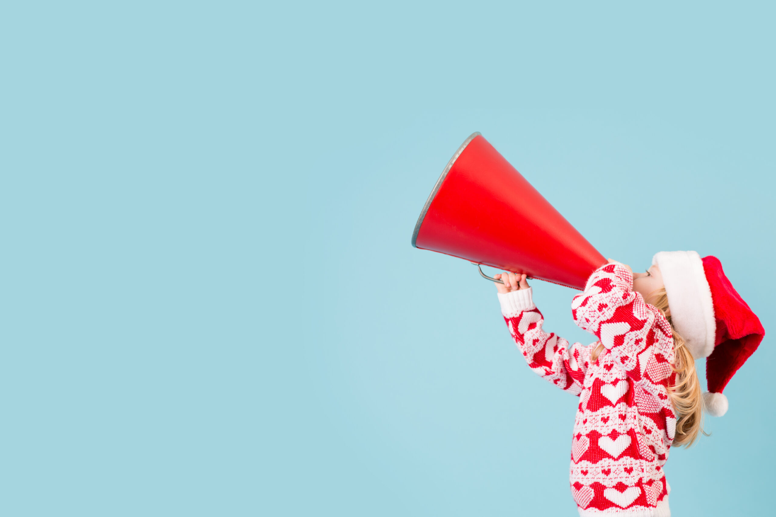 Little Christmas Girl in Santa Hat with Megaphone, Room for Text