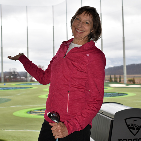 Carol poses in front of a driving range.