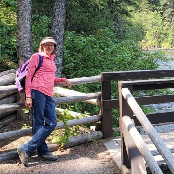 Carol poses for camera on a bridge over a river.