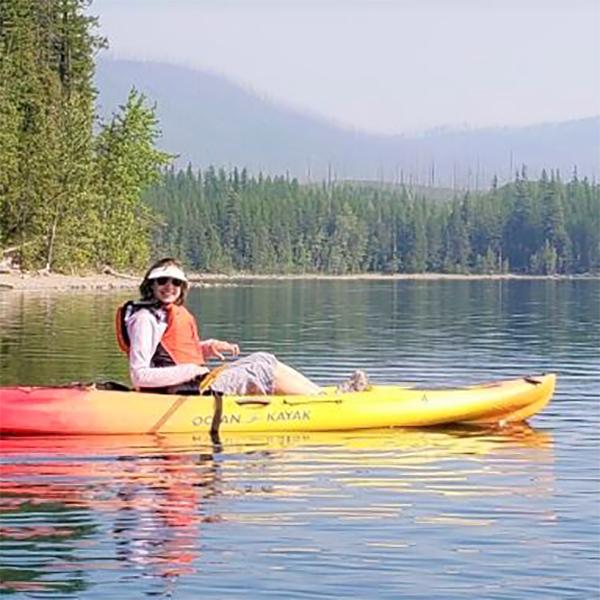 Carol kayaks on a lake.