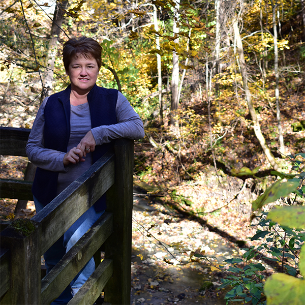 Peggy stands on a deck in the woods.