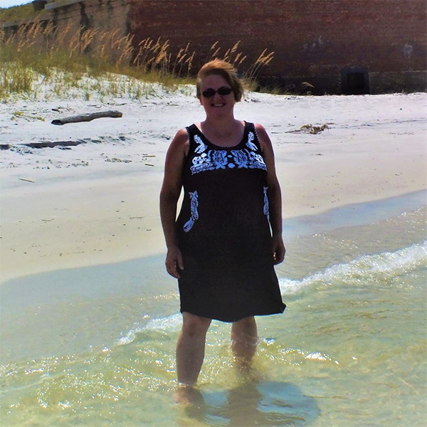 Peggy stands in the water on a sunny beach.