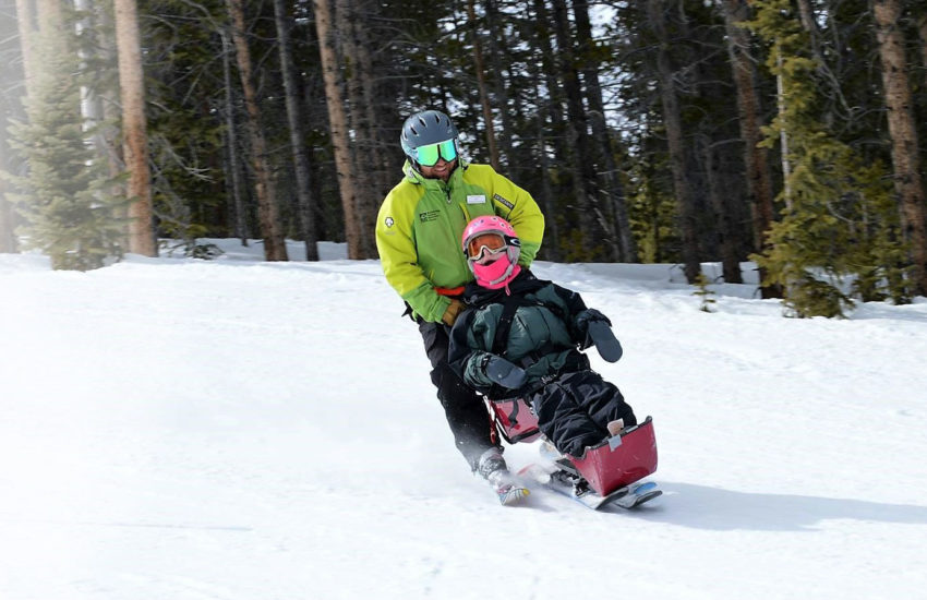 A young girl snow skiing with ski instructor.