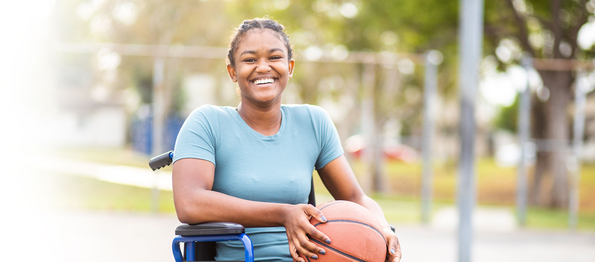 Young girl in wheelchair holding a basketball.
