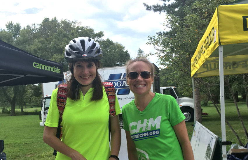 Two women smiling at a biking event.