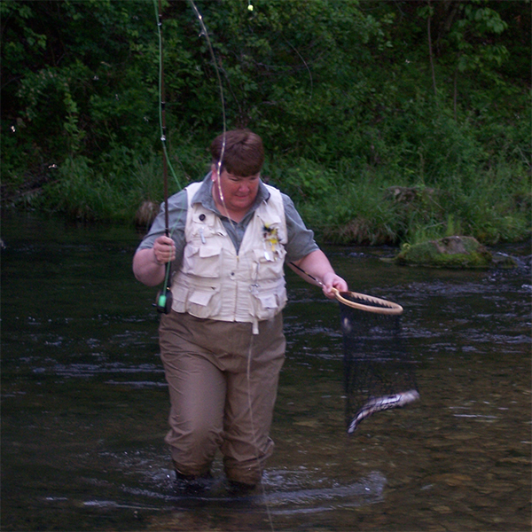 Susan stands in a river holding a fishing rod and a net with a fish in it.