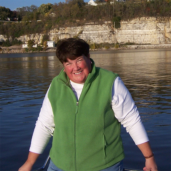 Susan smiles in front of a lake.