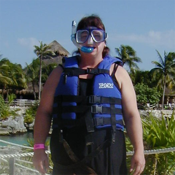 Vicky standing in front of palm trees wearing a snorkel and life vest.