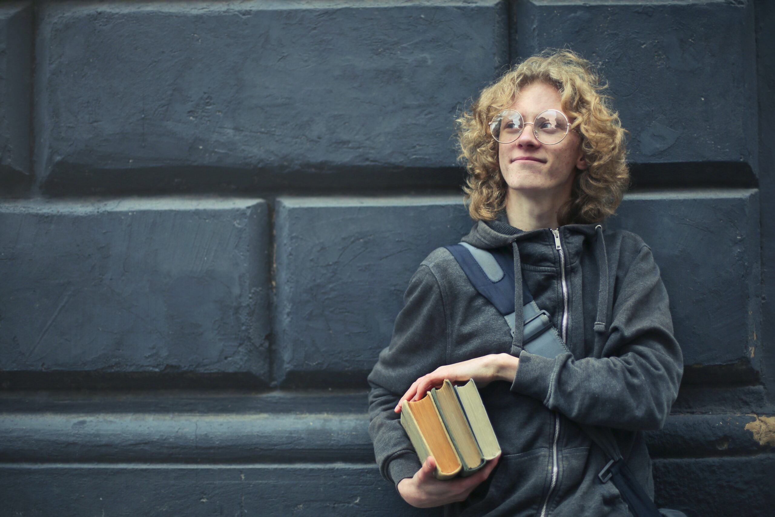 Student leaning against the wall holding books