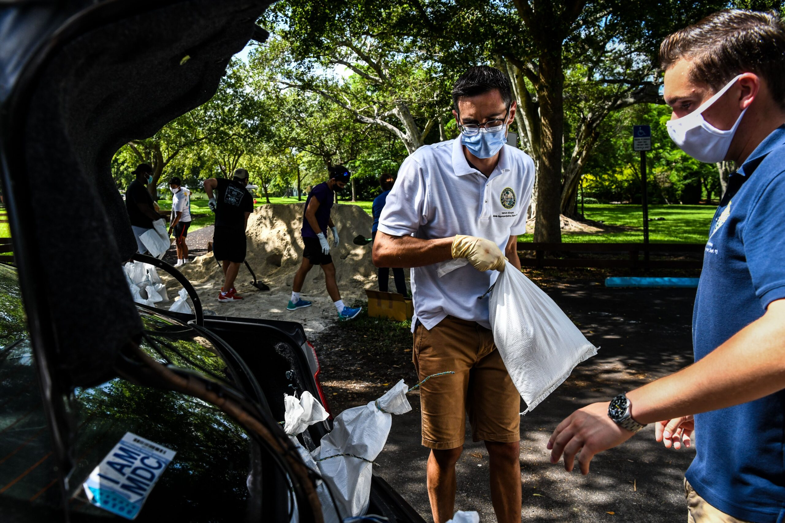 Member of Florida House of Representatives Vance Aloupis (C) puts sand bags in a resident's car trunk in Palmetto Bay near Miami, on July 31, 2020 as Floridians prepare for Hurricane Isaias while a State of Emergency has been declared for 19 Counties. - Hurricane Isaias lashed the Bahamas July 31 as it churned toward Florida, bringing new dangers to a US state suffering record deaths from an unrelenting coronavirus outbreak. The category one storm, packing winds of 75 miles (120 kilometers) an hour, gained strength Thursday night after sweeping over the Dominican Republic. (Photo by CHANDAN KHANNA / AFP) (Photo by CHANDAN KHANNA/AFP via Getty Images)