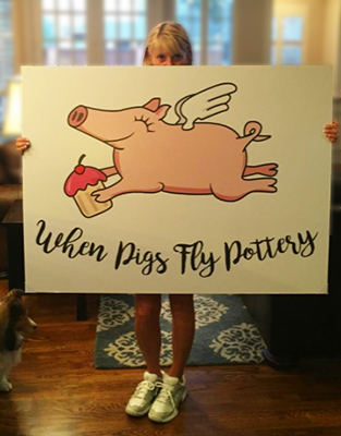 Becki holding When Pigs Fly Pottery poster