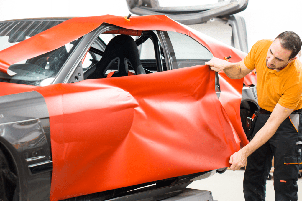 Black Car Being Wrapped in Red Vinyl