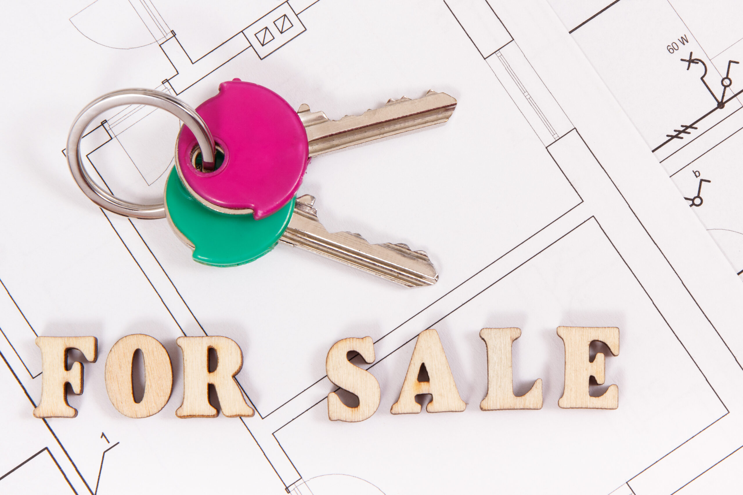Home keys with inscription for sale on construction housing plan, concept of selling or buying house