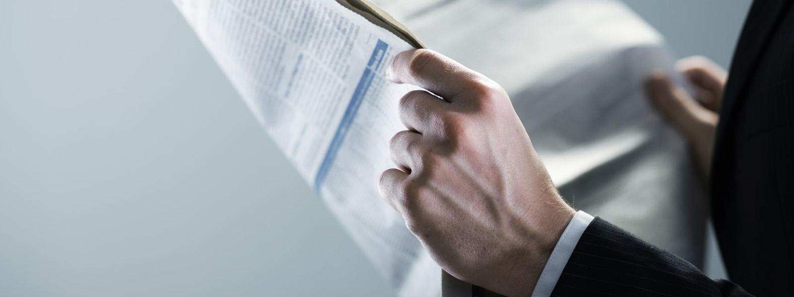 businessman holding newspaper in hands