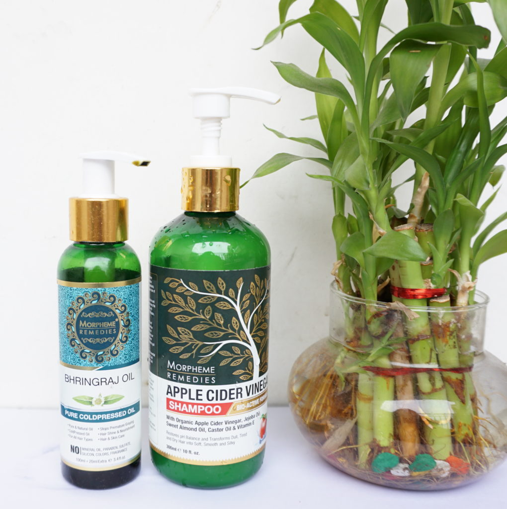 Morphme remedies brahmi hair oil and apple cider vinegar shampoo with a table plant