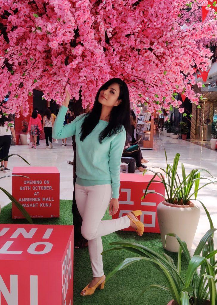 A-woman-standing-near-pink-flower-tree-in-white-skinny-jeans-mint-sweater