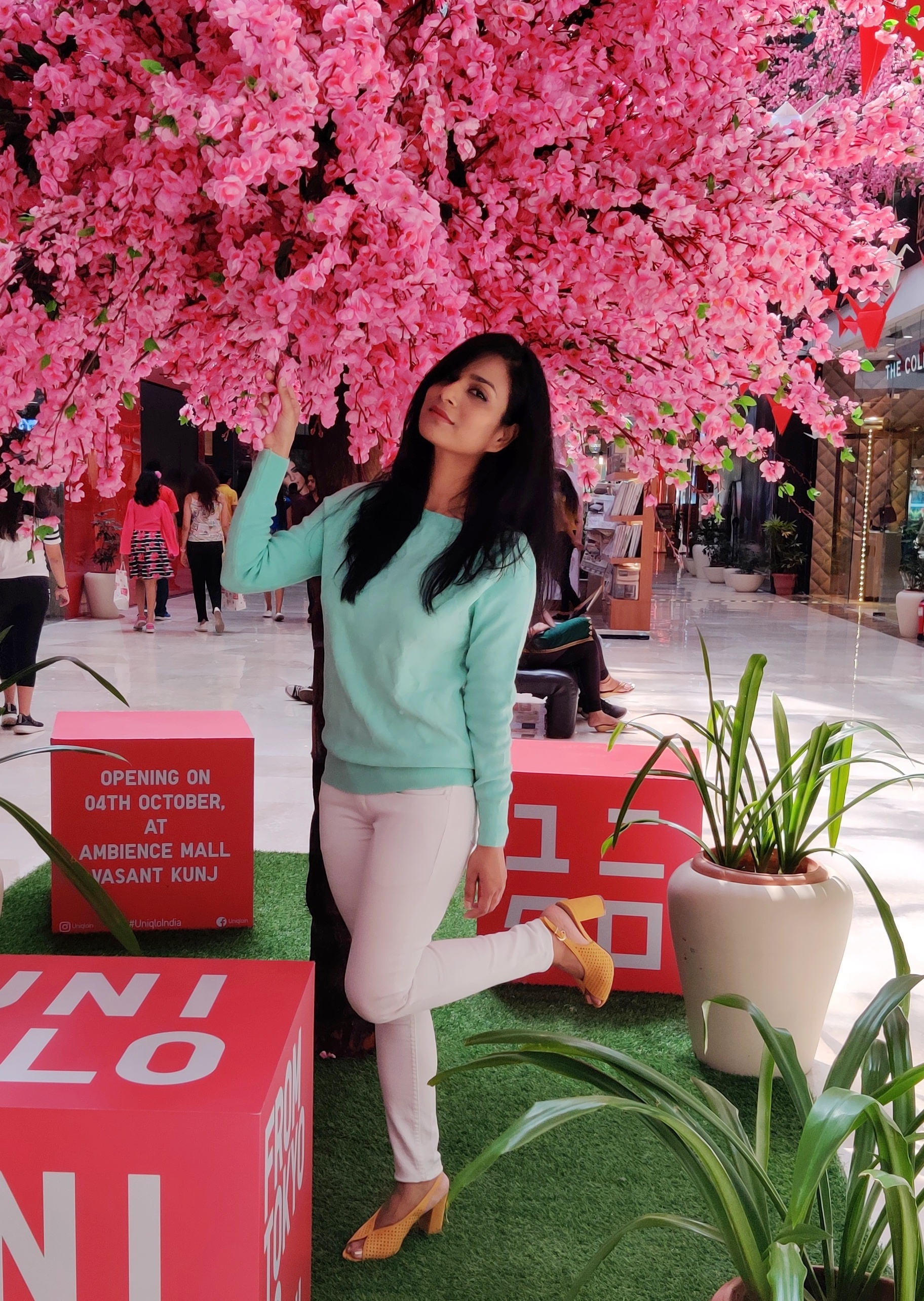 A-woman-standing-near-pink-flower-tree-in-white-skinny-jeans-mint-sweater