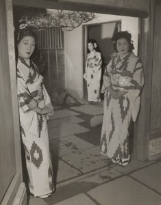 War era prositutes in traditional dress stand at a brothel doorway