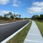 A paved section of the new Caruso Road with curb and sidewalk