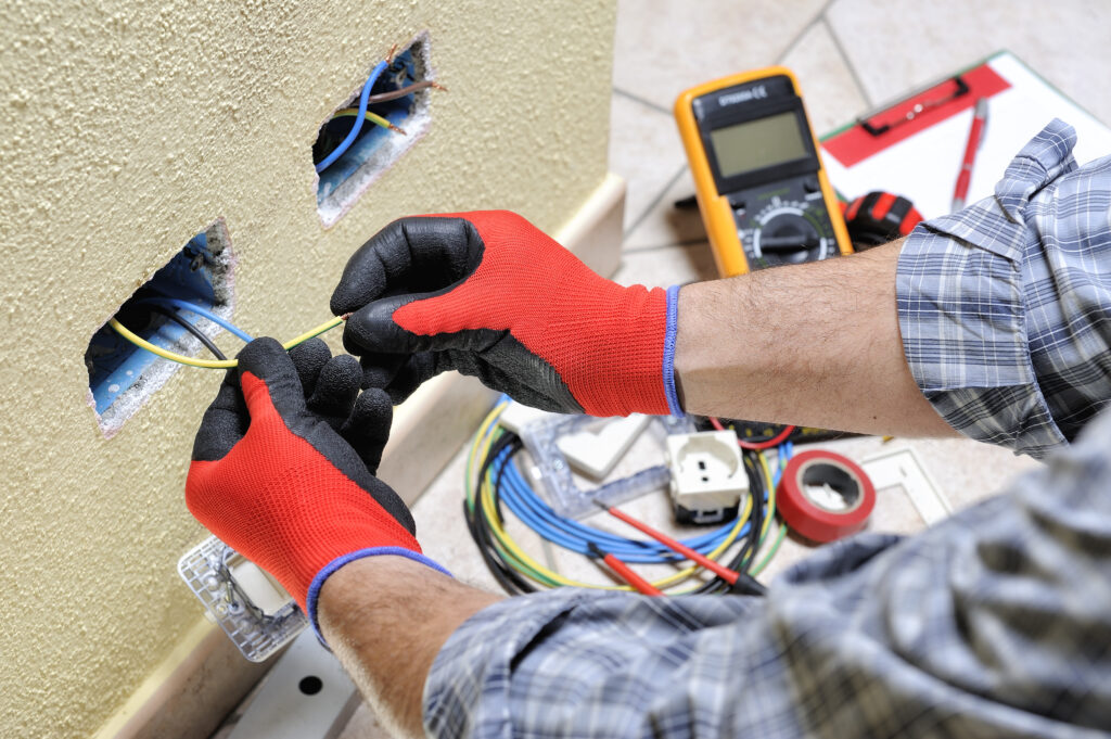 Electrician technician at work with safety equipment on a reside