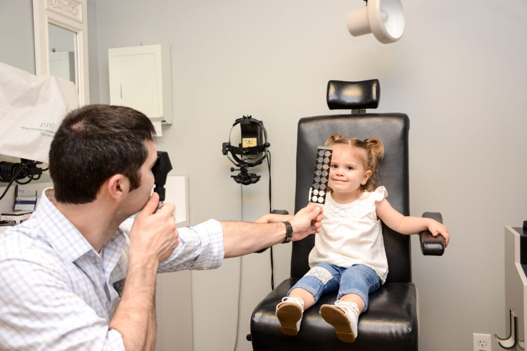 Dr Thirion performing a children's eye exam on a patient in network with soonercare. Best Eye Doctor Broken Arrow.