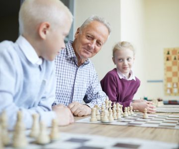 Smiling grandfather in checked shirt teaching his two curious grandkids how to play chess (zh translation)