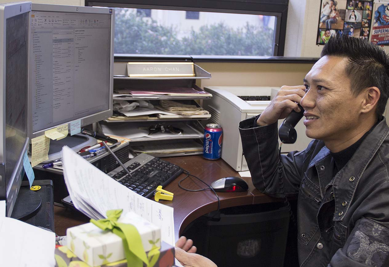 Senior Secretary of Academic Affairs Aaron Chan answers his telephone at his desk in room 8213 in Woodland Hills, Calif. on Dec. 11. Photo: Kristen Aslanian