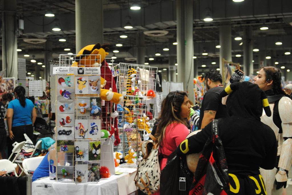Attendees in cosplay stand in front of a booth inside the Anime Expo's Artist Alley in Los Angeles, Calif. Photo by Jose Herrera.