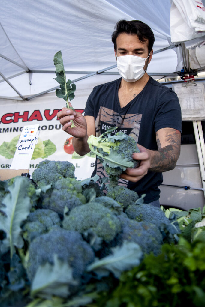 Carlos Chaves places brocoli on the C. Chavez farm stand at the Encino Farmers Market in Van Nuys, Calif., on April 4, 2020. Photo by Katya Castillo.