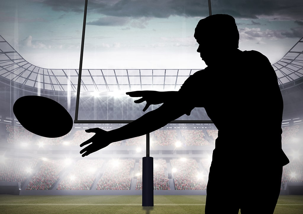 Silhouette of player catching a rugby ball in stadium