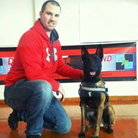 Policeman kneeling next to police dog