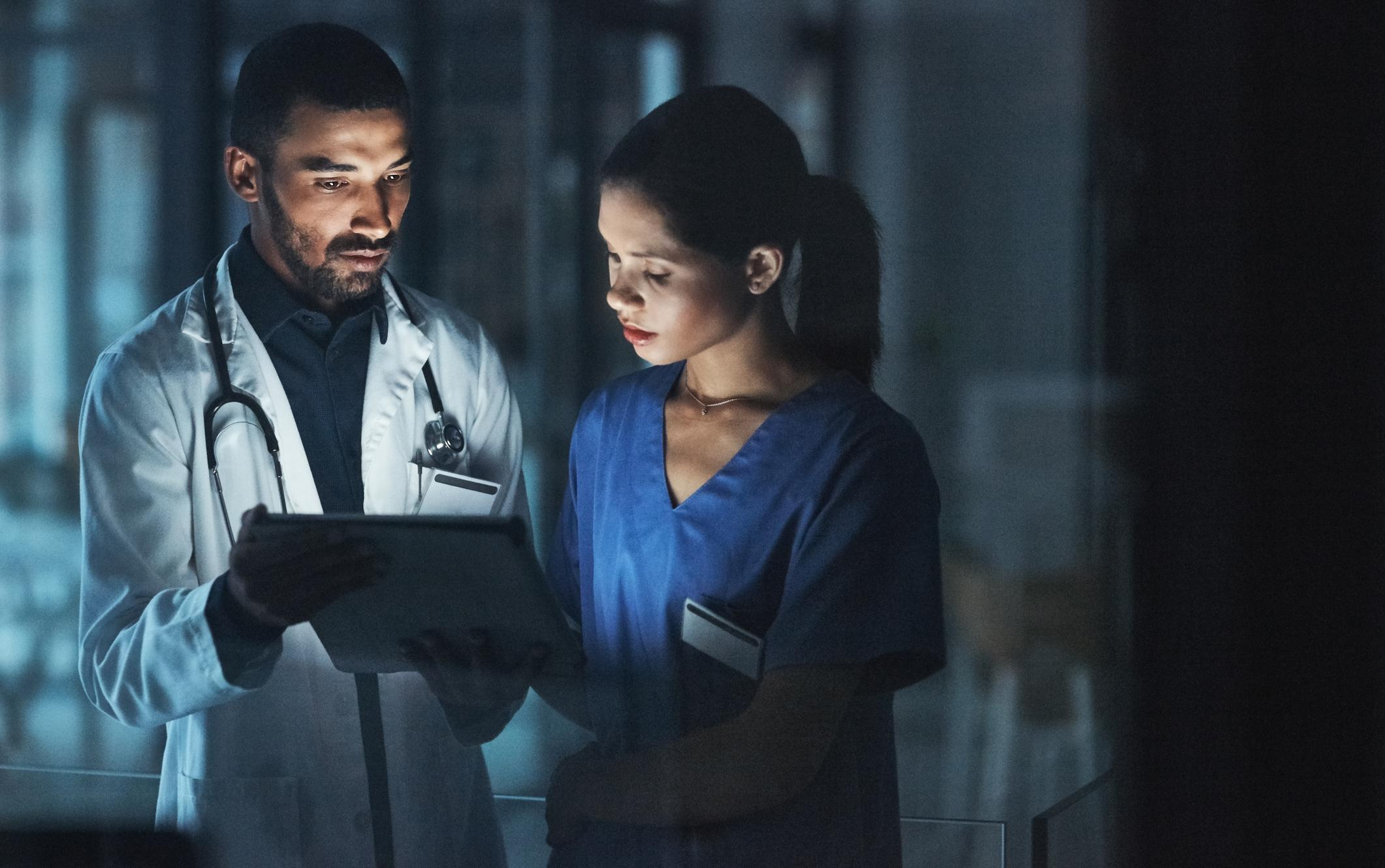 Shot of two young doctors using a digital tablet late at night in a modern hospital