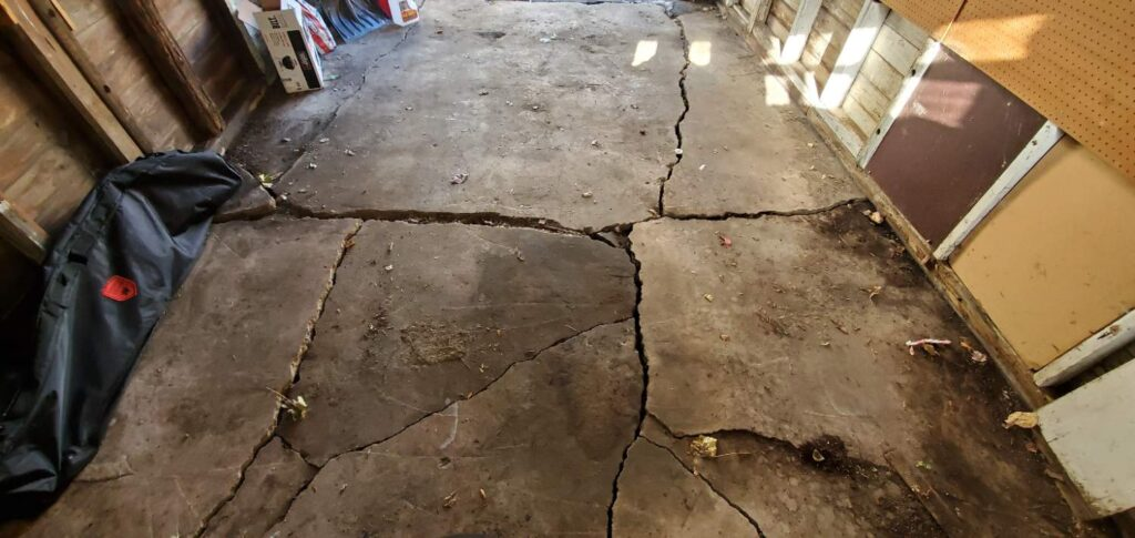 structural damage to garage floor caused by soil movement