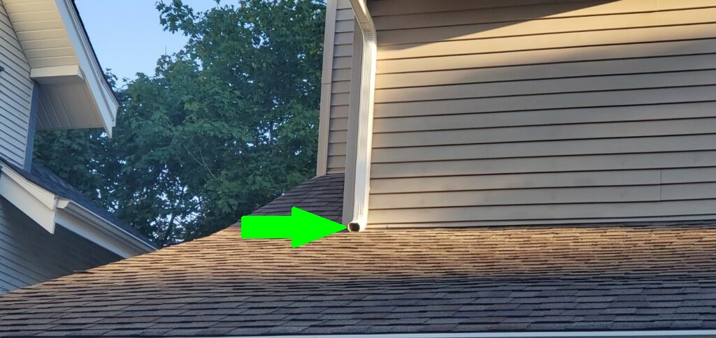 Downspout discharge to roof which can cause damage to roof covering