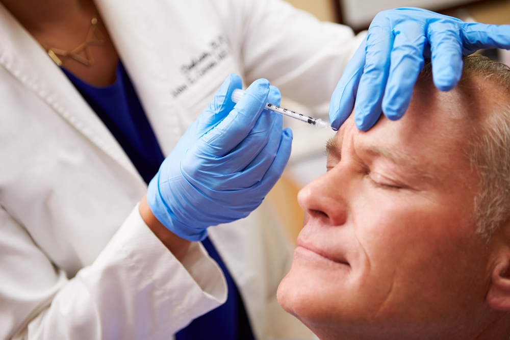 aging man getting botox injection to fight wrinkles