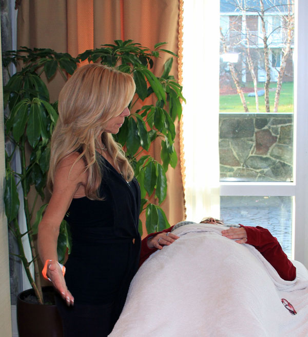 Karen Shaw Reiki Master with arms at her sides next to table with client lying down.