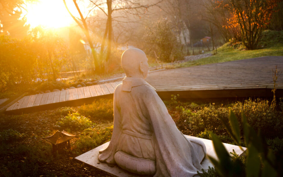 A statue of a meditating monk sits in our garden.