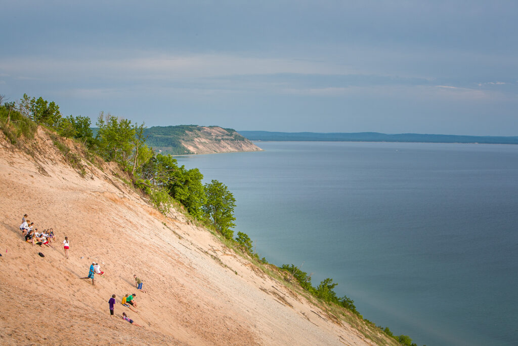Dune climbers descending the 400 feet to Lake Michigan, with the Empire Bluffs in the distance.