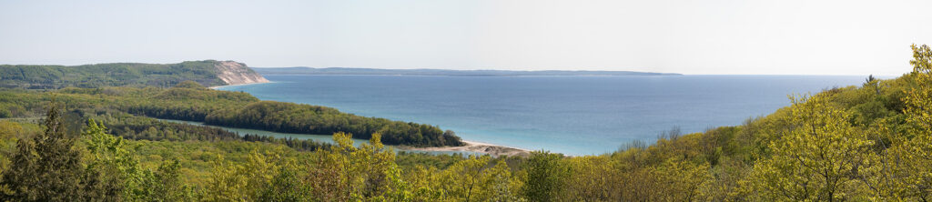 A panoramic view of Lake Michigan with the Empire Bluffs and North Bar Lake in the background, taken from the heights of the Sleeping Bear Dunes.