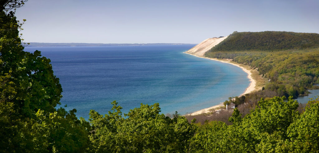 An iconic view of the Sleeping Bear Dune across Lake Michigan and the Manitou Passage from the Empire Bluffs trail.