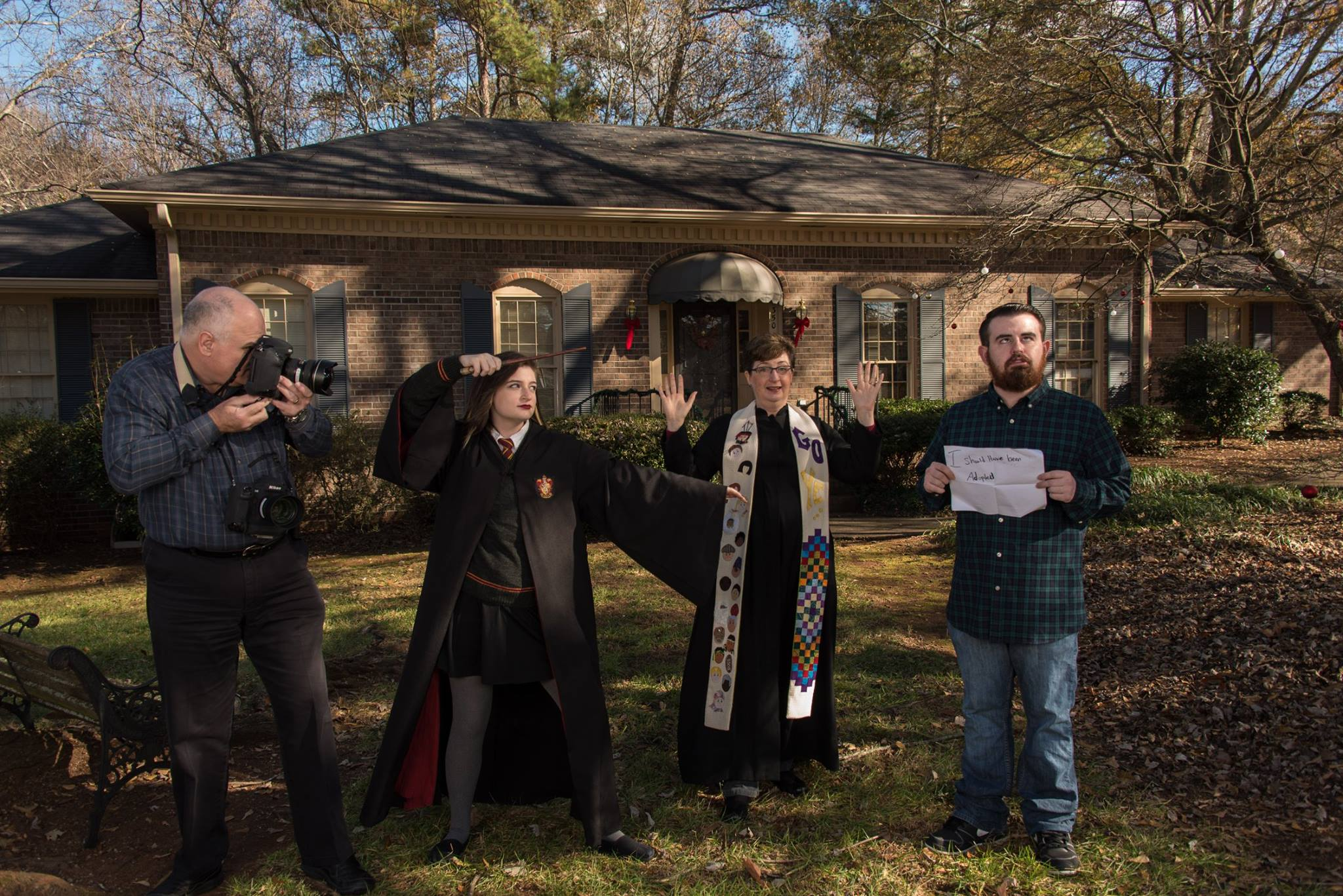 "The front of our annual Christmas card this year featured our daughter in her Hogwarts robe casting a spell on her brother, while I, in my clerical robe and stole, held up my hands to stop her and Stanley documented the action with his camera. A totally silly photo. Taylor's sign reads, ""I should have been adopted."" since he is always shaking his head at our silly antics."